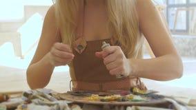 Ο ζωγράφος γυναικών εξωθεί στα ελαιοχρώματα παλετών των διαφορετικών χρωμάτων απόθεμα βίντεο
