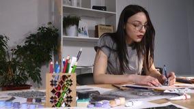 Ο ζωγράφος γυναικών εργάζεται σε ένα σκίτσο καθμένος στο γραφείο της Φορά τα γυαλιά φιλμ μικρού μήκους