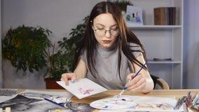Ο ζωγράφος γυναικών εργάζεται σε ένα σκίτσο καθμένος στο γραφείο της Φορά τα γυαλιά απόθεμα βίντεο
