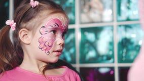 Ο ζωγράφος κάνει τη μορφή πεταλούδων στο πρόσωπο κοριτσιών ` s απόθεμα βίντεο