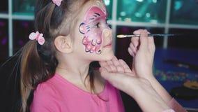 Ο ζωγράφος κάνει τη μορφή πεταλούδων στο πρόσωπο κοριτσιών ` s φιλμ μικρού μήκους