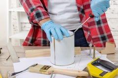 Ο ζωγράφος σπιτιών ανοίγει ένα δοχείο του χρώματος με ένα κατσαβίδι Στοκ Φωτογραφίες