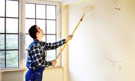 Ο ζωγράφος σπιτιών εργαζομένων χρωμάτισε τους τοίχους σε κίτρινο Στοκ Εικόνες
