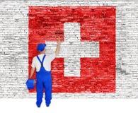 Ο ζωγράφος σπιτιών καλύπτει τον τοίχο με τη σημαία της Ελβετίας Στοκ Φωτογραφίες