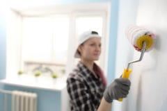 Ο ζωγράφος, ο σχεδιαστής και ο εργαζόμενος κοριτσιών χρωματίζουν έναν κύλινδρο και βουρτσίζουν τον τοίχο Χαμόγελο, που λειτουργεί Στοκ Φωτογραφία