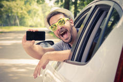 Οδηγός αυτοκινήτων που παρουσιάζει smartphone με την κενή οθόνη Στοκ εικόνες με δικαίωμα ελεύθερης χρήσης