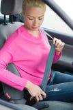 Οδηγός γυναικών που στερεώνει τη ζώνη ασφαλείας της Στοκ φωτογραφία με δικαίωμα ελεύθερης χρήσης