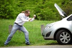 Οδηγός εξαγριωμένος ένα σπασμένο αυτοκίνητο Στοκ Φωτογραφία