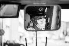 Οδηγός λεωφορείου πόλεων του Κιότο που φορά τη μάσκα στην εργασία, Ιαπωνία Στοκ Φωτογραφίες