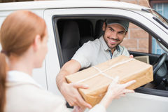 Οδηγός παράδοσης που δίνει το δέμα στον πελάτη στο φορτηγό του Στοκ Εικόνες