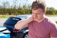 Οδηγός που πάσχει από το χτύπημα στο λαιμό μετά από τη σύγκρουση κυκλοφορίας Στοκ Εικόνες
