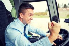 0 οδηγός που παρουσιάζει πυγμή και που οδηγεί το λεωφορείο Στοκ εικόνες με δικαίωμα ελεύθερης χρήσης