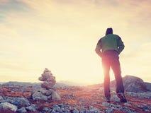 Οδηγός τουριστών στις εφοδιασμένες πέτρες στην αιχμή Άλπεων Ο ισχυρός οδοιπόρος απολαμβάνει το ηλιοβασίλεμα στο αλπικό βουνό Στοκ φωτογραφίες με δικαίωμα ελεύθερης χρήσης