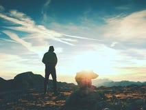 Οδηγός τουριστών στις εφοδιασμένες πέτρες στην αιχμή Άλπεων Ο ισχυρός οδοιπόρος απολαμβάνει το ηλιοβασίλεμα στο αλπικό βουνό Στοκ Εικόνες