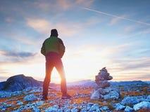 Οδηγός τουριστών στις εφοδιασμένες πέτρες στην αιχμή Άλπεων Ο ισχυρός οδοιπόρος απολαμβάνει το ηλιοβασίλεμα στο αλπικό βουνό Στοκ Φωτογραφίες