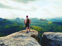 Οδηγός τουριστών σχετικά με το δύσκολο σημείο άποψης με τους πόλους διαθέσιμους Οδοιπόρος με τη φίλαθλη στάση σακιδίων πλάτης στο Στοκ εικόνα με δικαίωμα ελεύθερης χρήσης