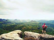 Οδηγός τουριστών σχετικά με το δύσκολο σημείο άποψης με τους πόλους διαθέσιμους Οδοιπόρος με τη φίλαθλη στάση σακιδίων πλάτης στο Στοκ Εικόνες