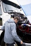 Οδηγός φορτηγού που ελέγχει το ημι φορτηγό μηχανών λειτουργίας με την ανοικτή κουκούλα Στοκ εικόνα με δικαίωμα ελεύθερης χρήσης