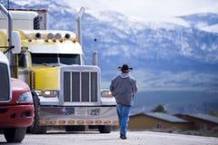 Οδηγός φορτηγού που πηγαίνει στο προσαρμοσμένο εντυπωσιακό κίτρινο ημι φορτηγό Στοκ φωτογραφία με δικαίωμα ελεύθερης χρήσης