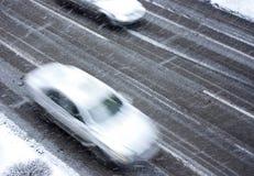 Οδηγώντας αυτοκίνητα στη χιονώδη οδό πόλεων στη θαμπάδα κινήσεων Στοκ Φωτογραφία