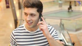 Οδηγώντας κυλιόμενη σκάλα νεαρών άνδρων στη λεωφόρο αγορών στο κινητό τηλέφωνο απόθεμα βίντεο
