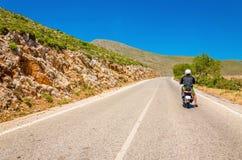 Οδηγώντας μηχανικό δίκυκλο νεαρών άνδρων στον κενό δρόμο ασφάλτου, ελληνικό Κα νησιών Στοκ εικόνες με δικαίωμα ελεύθερης χρήσης