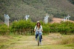 Οδηγώντας ποδήλατο γυναικών στον τομέα στοκ εικόνα