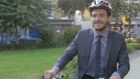 Οδηγώντας ποδήλατο επιχειρηματιών μέσω του πάρκου πόλεων απόθεμα βίντεο