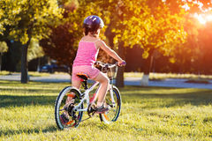 Οδηγώντας ποδήλατο κοριτσιών παιδιών στο θερινό ηλιοβασίλεμα στο πάρκο Στοκ εικόνα με δικαίωμα ελεύθερης χρήσης