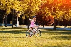 Οδηγώντας ποδήλατο κοριτσιών παιδιών στο θερινό ηλιοβασίλεμα στο πάρκο Στοκ εικόνες με δικαίωμα ελεύθερης χρήσης