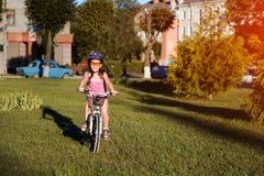 Οδηγώντας ποδήλατο κοριτσιών παιδιών στο θερινό ηλιοβασίλεμα στο πάρκο Στοκ φωτογραφίες με δικαίωμα ελεύθερης χρήσης