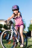 Οδηγώντας ποδήλατο κοριτσιών παιδιών στο θερινό ηλιοβασίλεμα στο πάρκο Στοκ Εικόνες