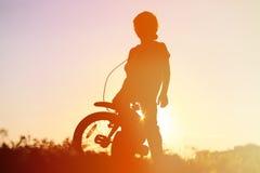 Οδηγώντας ποδήλατο μικρών παιδιών στο ηλιοβασίλεμα, αθλητισμός παιδιών στοκ φωτογραφίες