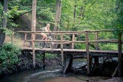 Οδηγώντας ποδήλατο νέων κοριτσιών σε μια ξύλινη γέφυρα στοκ εικόνα