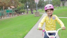 Οδηγώντας ποδήλατο νέων κοριτσιών στο πάρκο που εξετάζει τη κάμερα απόθεμα βίντεο