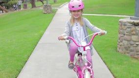 Οδηγώντας ποδήλατο νέων κοριτσιών στο πάρκο που εξετάζει τη κάμερα φιλμ μικρού μήκους