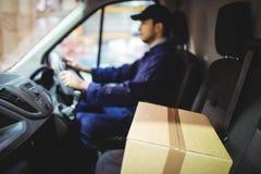Οδηγώντας φορτηγό οδηγών παράδοσης με τα δέματα στο κάθισμα στοκ φωτογραφία