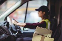 Οδηγώντας φορτηγό οδηγών παράδοσης με τα δέματα στο κάθισμα στοκ εικόνες