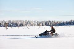 Οδηγώντας όχημα για το χιόνι ατόμων στη Φινλανδία στοκ εικόνες