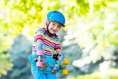 Οδηγώντας skateboard παιδιών στο θερινό πάρκο Στοκ Φωτογραφία