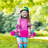 Οδηγώντας skateboard παιδιών στο θερινό πάρκο Στοκ Εικόνα