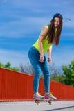 Οδηγώντας skateboard σκέιτερ κοριτσιών εφήβων στην οδό Στοκ Φωτογραφίες
