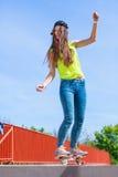Οδηγώντας skateboard σκέιτερ κοριτσιών εφήβων στην οδό Στοκ Εικόνες