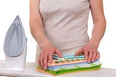 Ο ηλεκτρικός σίδηρος και τα θηλυκά χέρια συσσωρεύουν το καθαρό λινό, που απομονώνεται στο λευκό Στοκ φωτογραφίες με δικαίωμα ελεύθερης χρήσης