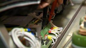 Ο ηλεκτρολόγος εγκαθιστά τα συνδέοντας καλώδια τηλεφωνικών κέντρων με το εργαλείο φιλμ μικρού μήκους