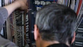 Ο ηλεκτρολόγος κόβει τα καλώδια με τις πένσες εγκαθιστώντας το τηλεφωνικό κέντρο απόθεμα βίντεο