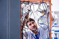 Ο ηλεκτρολόγος που προσπαθεί να ξεμπερδεψει τα καλώδια στην έννοια επισκευής στοκ φωτογραφίες