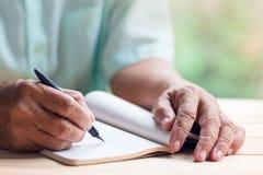 Ο ηληκιωμένος γράφει στην κενή σελίδα σημειωματάριων Στοκ εικόνα με δικαίωμα ελεύθερης χρήσης