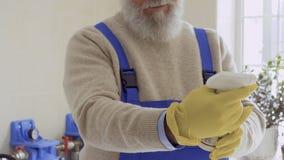 Ο ηληκιωμένος διάβασε την οδηγία του προϊόντος καθαρισμού φιλμ μικρού μήκους