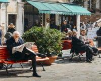 Ο ηληκιωμένος διαβάζει μια τοπική ιταλική εφημερίδα σε έναν τετραγωνικό πάγκο που περιβάλλεται από την αναταραχή Στοκ εικόνες με δικαίωμα ελεύθερης χρήσης
